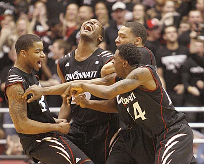 Cincinnati players begin celebrating as the Bearcats' second successive 20-victory season becomes a reality.  (AP)