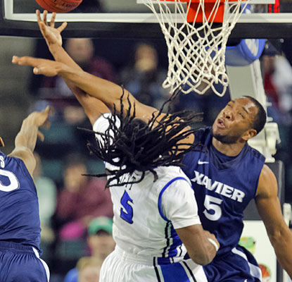 Jordair Jett draws the foul, but Dezmine Wells has the last word, scoring 18 points in Xavier's victory.  (US Presswire)