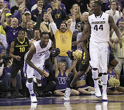 Washington's Tony Wroten (left) reacts after his dunk late in the second half. Darnell Gant (44) and UW fans also look pleased. (AP)