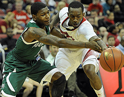 Louisville guard Russ Smith steals the ball from Manhattan's CJ Jones. Smith scores 23 points for the Cardinals. (US Presswire)