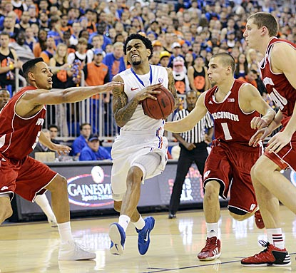 Florida guard Mike Rosario drives in between Wisconsin's Ryan Evans (5), Ben Brust (1) and Jared Berggren (40).  (AP)