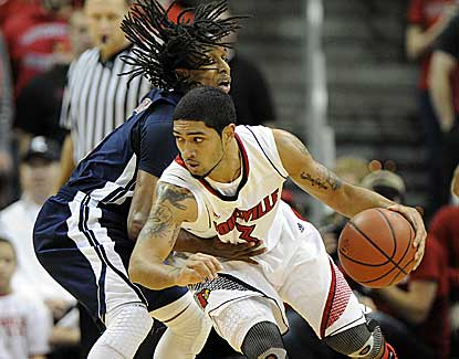Louisville's Peyton Siva drops his shoulder against Russell Wilson in the Cards' win over Samford. (US Presswire)
