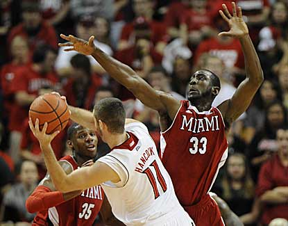 Louisville's Luke Hancock is pressured by Miami (Ohio)'s Will Felder (33) and Jon Harris (35). (US Presswire)