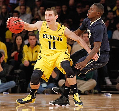 Michigan freshman Nik Stauskas, guarded here by Pittsburgh's Tray Woodall, scores 15 points off the bench.  (Getty Images)