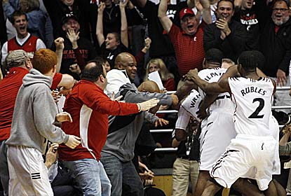Cashmere Wright is mobbed after his fadeaway jumper wins it for for No. 17 Cincinnati in a matchup of unbeaten teams. (US Presswire)
