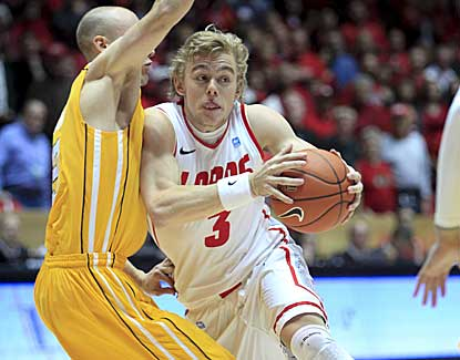 New Mexico's Hugh Greenwood drives around Valparaiso's Will Bogan on Saturday night. (AP)