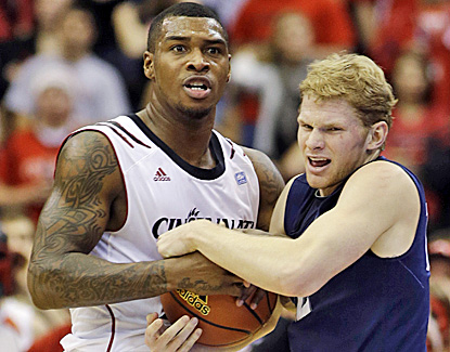 Sean Kilpatrick (left) ties up Xavier's Brad Redford during Cincinnati's win. Kilpatrick scores a game-high 25 points. (AP)