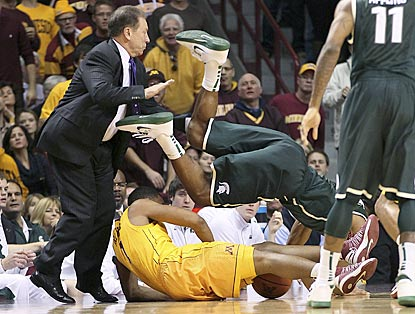 Tom Izzo (left) avoids getting wiped out as Minnesota's Andre Hollins (bottom) and MSU's Gary Harris compete for a loose ball. (AP)