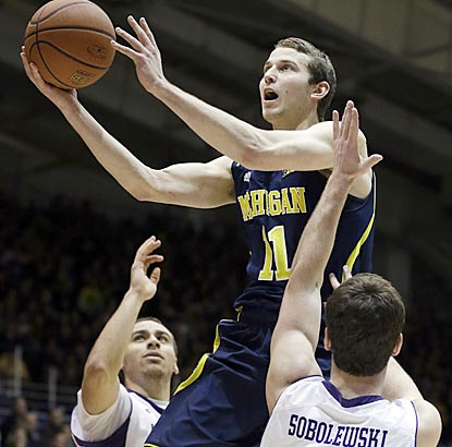 Michigan guard Nik Stauskas drives to the basket between Northwestern guards Tre Demps (left) and Dave Sobolewski.  (AP)