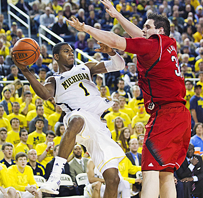 Michigan's Glenn Robinson III, who scores 14 points, tries to keep the ball inbounds as Nebraska's Andre Almeida defends. (AP)