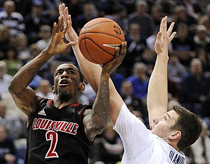 Louisville's Russ Smith, who scores a game-high 23 points, shoots around UConn's Tyler Olander. (AP)