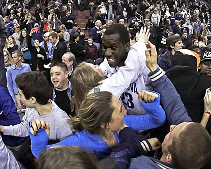Villanova's Daniel Ochefu is mobbed by fans after the Wildcats upend the Cardinals for a much-needed victory.  (AP)