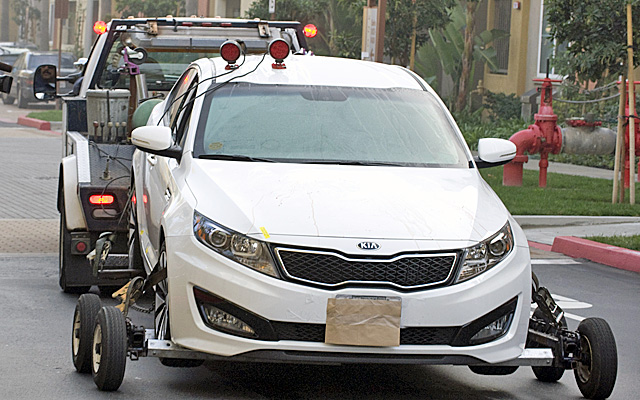 The Kia sedan where Quan and Lawrence were found shot to death is removed from the property. (AP)