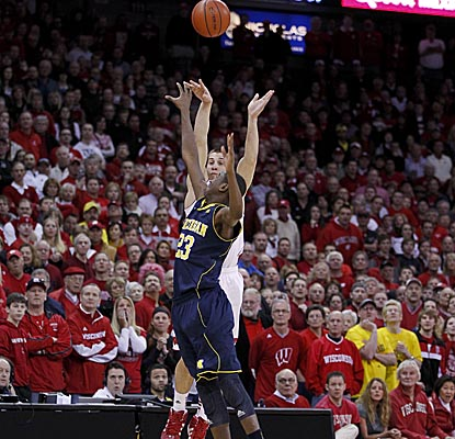 Ben Brust lets fly two steps past halfcourt to send it into overtime, where the Badgers knock off Big Ten-rival Michigan. (AP)