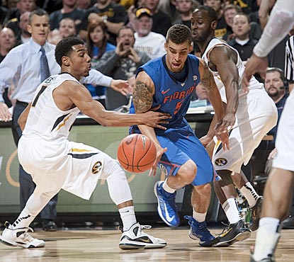 Florida's Scottie Wilbekin loses control of the ball as he drives between Missouri's Phil Pressey (left) and Keion Bell.  (AP)