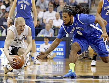 Brad Redford (left) and Saint Louis guard Jordair Jett scramble for a loose ball as Xavier pulls out a win in overtime. (AP)