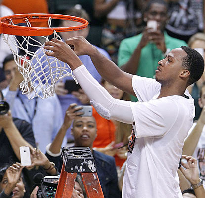 Kenny Kadji leads Miami with 23 points then helps cut down the net as the Canes celebrate their first ACC title.  (USATSI)