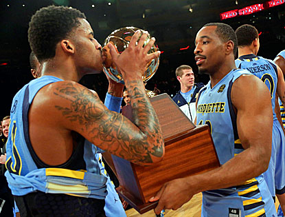 Vander Blue, who scores the winning points, kisses the Big East trophy along with Derrick Wilson after Marquette's win. (AP)
