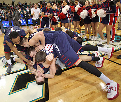 Libert players celebrate in a pile on the court after earning the Flames' first NCAA bid since 2004.  (AP)