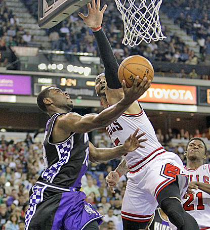 Tyreke Evans (left) drives in for two of his 26 points against Chicago's Carlos Boozer. (AP)
