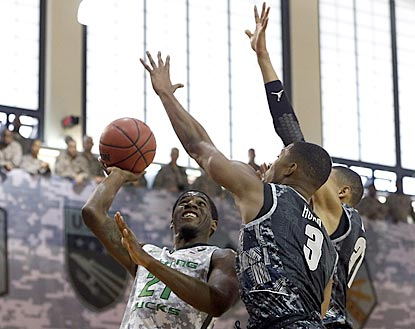 Oregon's Damyean Dotson (left) shoots over Georgetown defenders while U.S. servicemen look on at Camp Humphreys.  (USATSI)