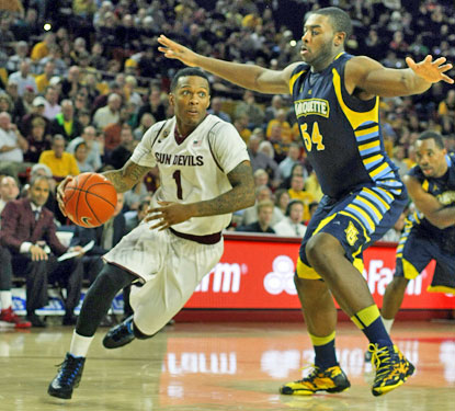 Jahii Carson, who scores 23 points, drives past Marquette's Davante Gardner during the Sun Devils' win. (USATSI)