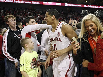 Nebraska's Tai Webster manuevers through the Cornhuskers faithful as they rush the court.  (USATSI)