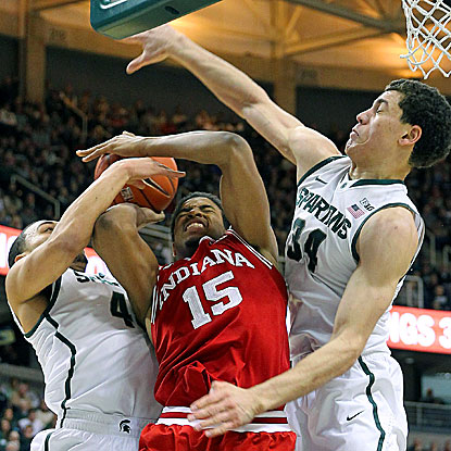Indiana's Devin Davis (center) is fouled by Michigan State's Denzel Valentine and Gavin Schilling (right).  (USATSI)