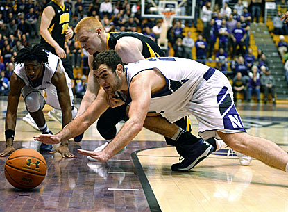 Northwestern's Alex Olah (right) and Iowa's Aaron White (top) hit the floor diving for a loose ball during the Hawkeyes' win. (USATSI)
