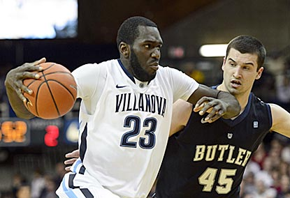 Daniel Ochefu, one of 10 players to score for Villanova, drives by Butler's Andrew Chrabascz during the first half.  (USATSI)