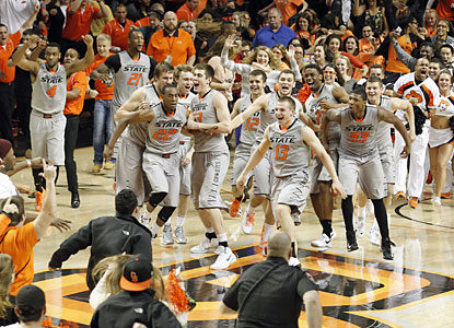 The Oklahoma State faithful storm the court after their team helps its NCAA tournament chances after taking down No. 5 Kansas. (USATSI)