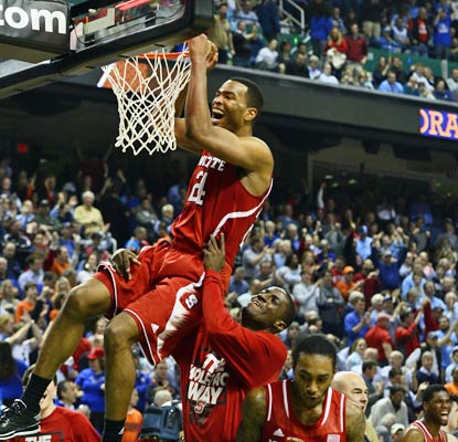 T.J. Warren hangs on the rim to celebrate a huge victory for NC State over Syracuse in Greensboro.  (USATSI)