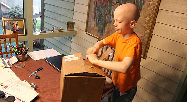 Russell, a child touched by Buzz Williams' kindness, opens a package from the coach. (Provided to CBSSports.com)
