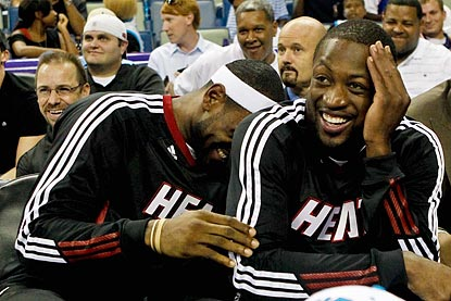 Dwyane Wade and LeBron James seem to be enjoying themselves while giving their ailing hamstrings a rest.  (US Presswire)