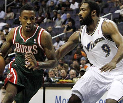 Gilbert Arenas (right) plays only three minutes against the Bucks before leaving with a strained groin.  (AP)