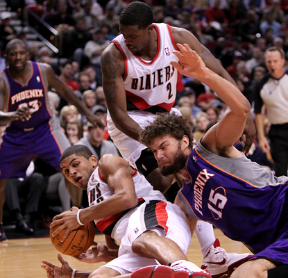 The Trail Blazers' Nicolas Batum (left) battles the Suns' Robin Lopez for possession in the season opener. (AP)
