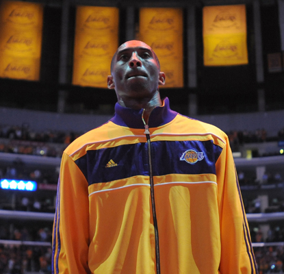 Kobe Bryant stands beneath his championship banners before scoring 27 against the Rockets in the season opener.   (AP)