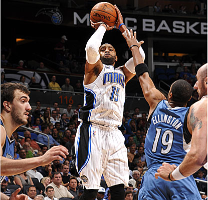 Vince Carter takes a shot over Timberwolves defenders during the Magic's 128-86 win.  (Getty Images)