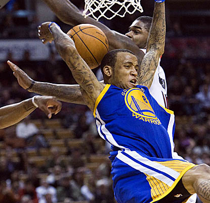 The NBA's leading scorer, Monta Ellis, twists awkwardly going to the hoop versus Toronto. (AP)