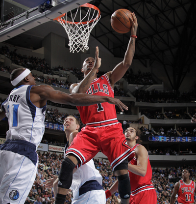The Bulls' Derrick Rose gets into the lane before scoring on a layup against the Mavericks' Dirk Nowitzki and Jason Terry. (US Presswire)