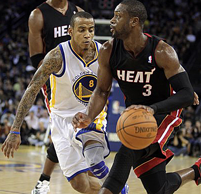 Dwyane Wade dribbles past Monta Ellis on his way to scoring 34 points in the Heat's seventh straight double-digit win. (AP)