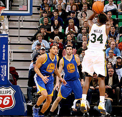 C.J. Miles stops and pops over Golden State defenders, finishing with 20 points in Utah's win. (Getty Images)