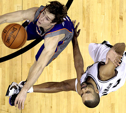 Tony Parker (right), who finishes with 19 points, is fouled here by the Suns' Goran Dragic. (AP)