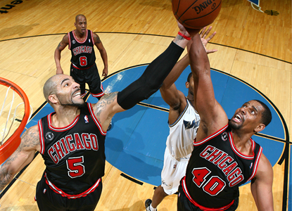 Carlos Boozer, left, and Kurt Thomas go up for a rebound against Hilton Armstrong of the Wizards during the Bulls' win. (Getty Images)