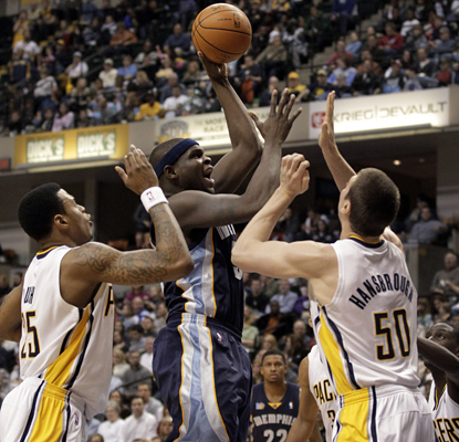 Zach Randolph shoots between Brandon Rush, left, and Tyler Hansbrough as he works toward his 18 points. (AP)