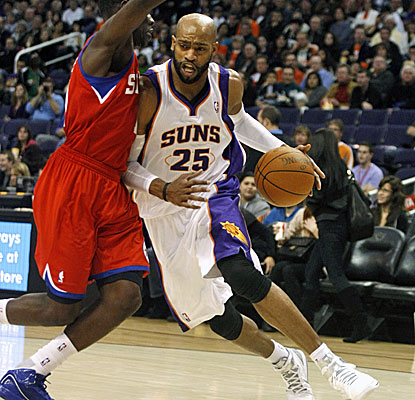 Vince Carter, right, is guarded by Jrue Holiday and scores 18 in his debut with the Suns. (AP)