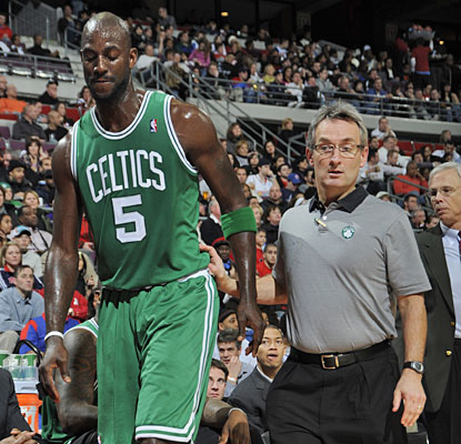 Kevin Garnett leaves the Palace floor with Celtics trainer Ed Lacerte after injuring his right calf.  (Getty Images)