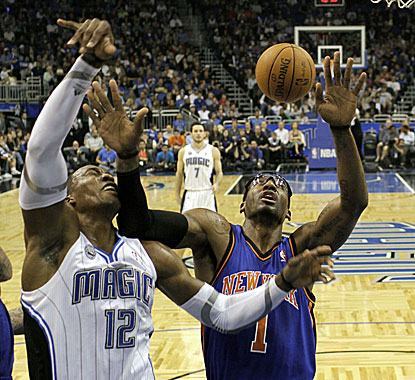 Magic center Dwight Howard takes an elbow to the chops while battling Amar'e Stoudemire for a rebound. (AP)