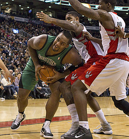 Boston's Glen Davis tries to drive through a trio of Raptors defenders in Toronto. (AP)