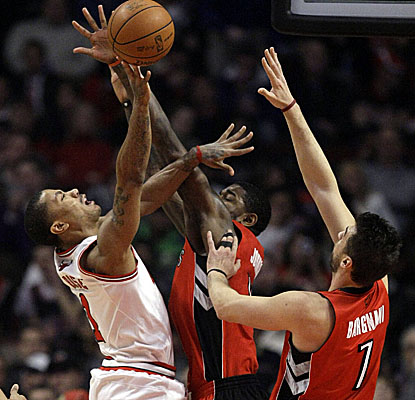 Toronto defenders give Derrick Rose a hard way to go, but the Bulls' star notches 19 points. (AP)
